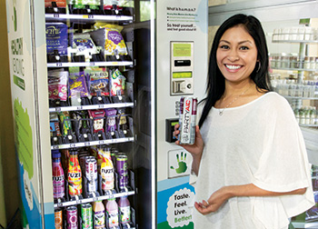 New-LivingWell_young woman poses with drink in front of machine